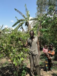 a small-scale farmer next to his coffee plant